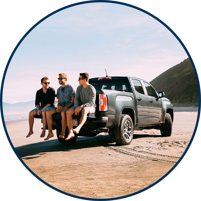 CPO Chevrolet Silverado on the beach with three people sitting on tailgate